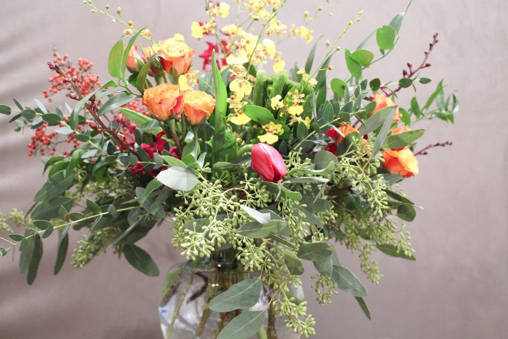 Orange, hot pink, yellow and red flowers mixed with greens in a glass vase.