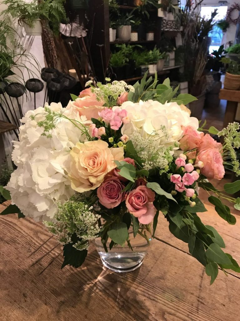 White, light pink and peach flowers mixed with greens in a glass vase.