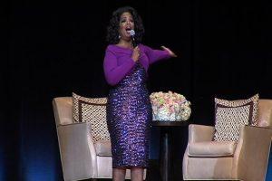 Oprah Winfrey on stage beside floral arrangement