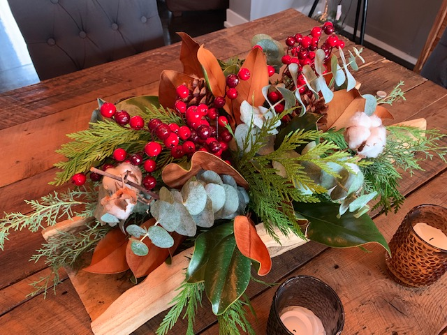 winter centerpiece with branches and berries in a log