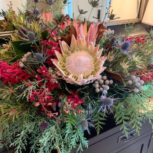 s front hall arrangement of protea, thistle, red Ashima orchids, leucadendron, Brazilia balls, juniper, cedar and magnolia